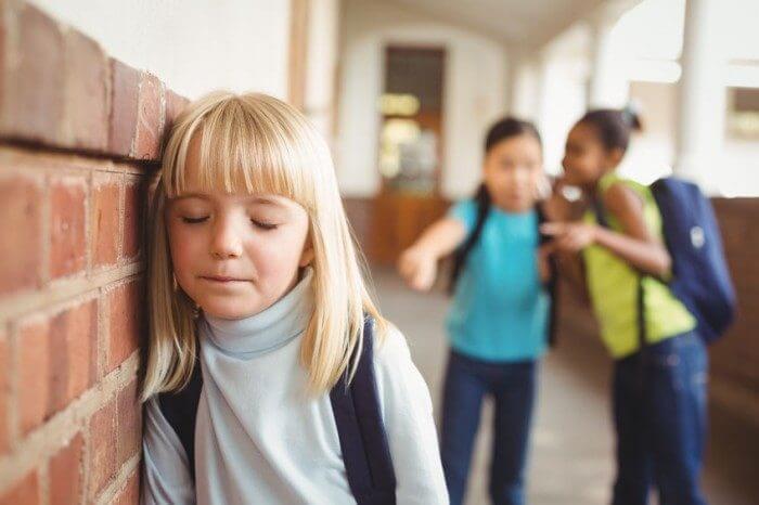 Petite fille moquée par deux camarades à l'école