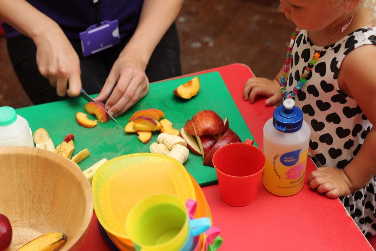 Adulte préparant un goûter sain de fruits pour une petite fille