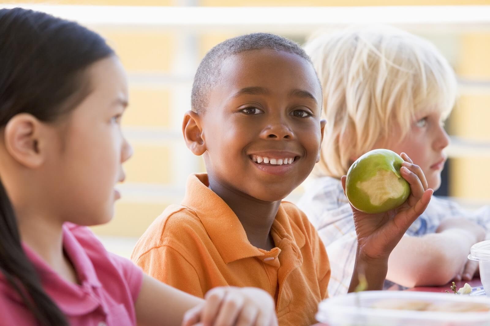 Un enfant avec une pomme croquée, une idée pour des goûters sains