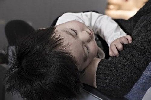 Un jeune enfant allongé dans les bras de sa maman.