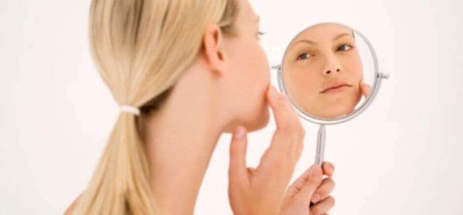 Une femme qui se regarde dans un miroir.