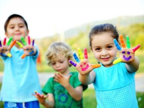 Ninos con las manos pintadas jugando