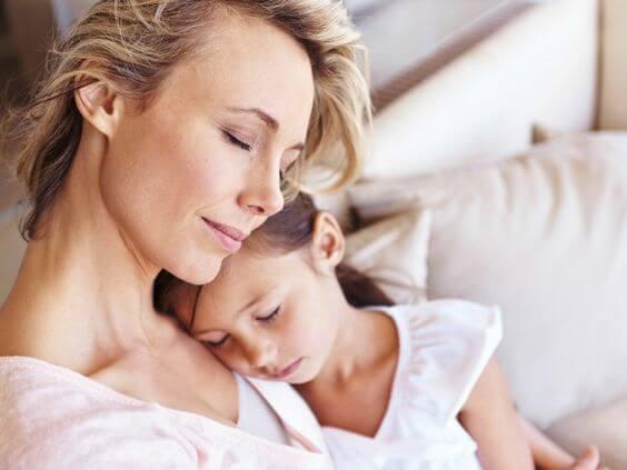 Petite fille endormie dans les bras de sa maman