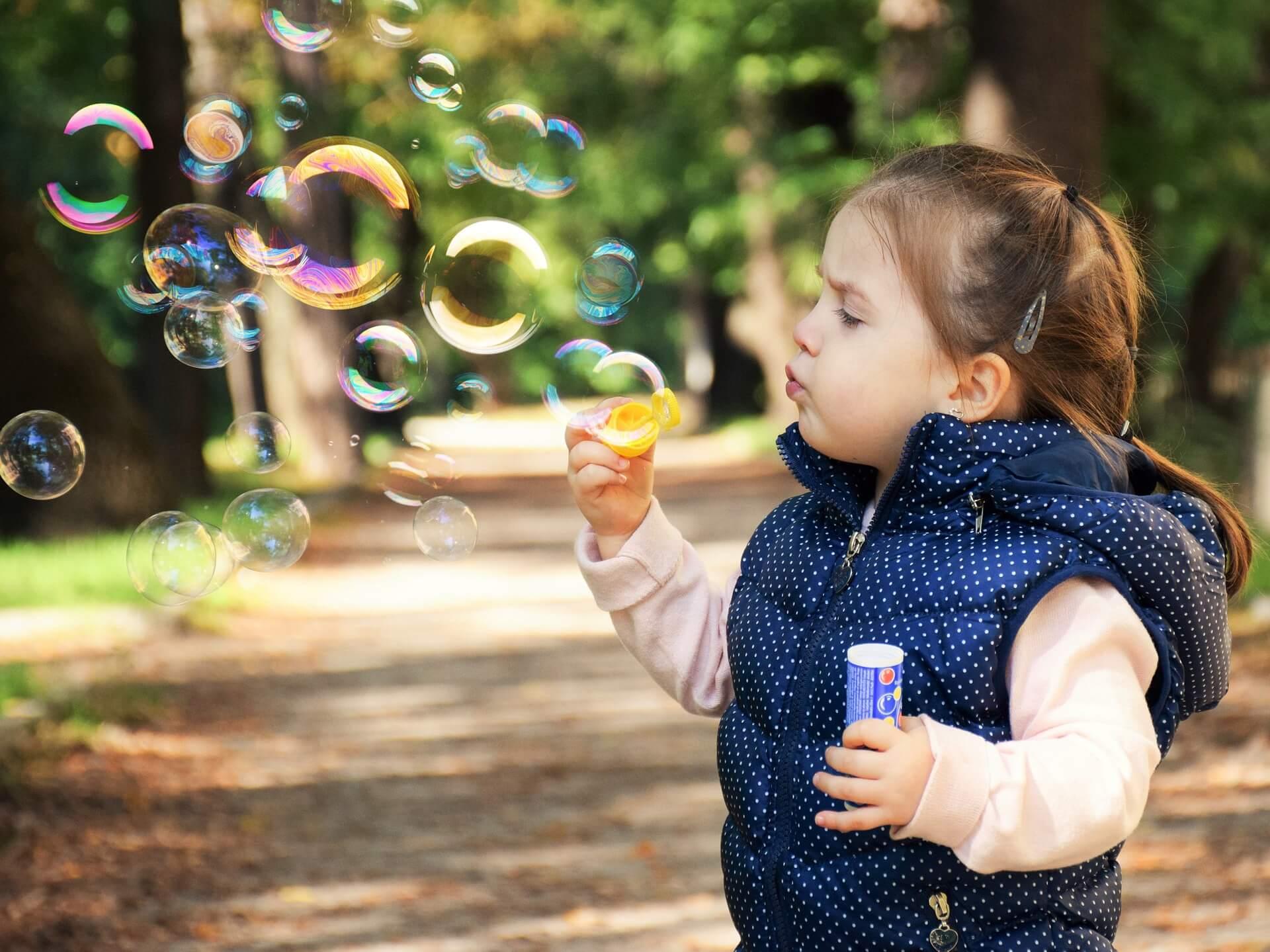 menina fazendo bolhas de sabão ao ar livre