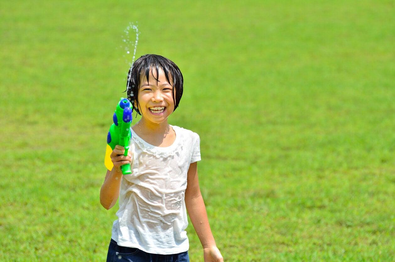 nina nena mojada agua pistola diversion juego feliz felicidad pasto aire libre verano prevencion insolacion golpe de calor refresca