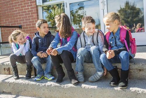 Un grupo de niños pequeños hablando en el patio a la salida del colegio