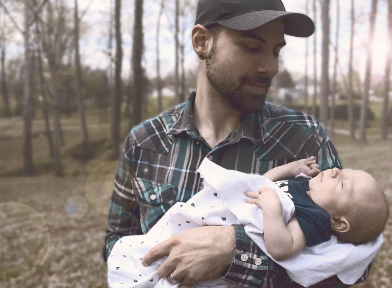 Padre con gorra con su bebe recien nacido