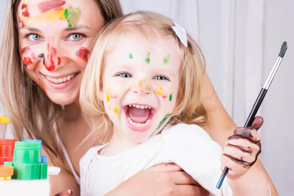 Madre e hija con la cara manchada de pintura