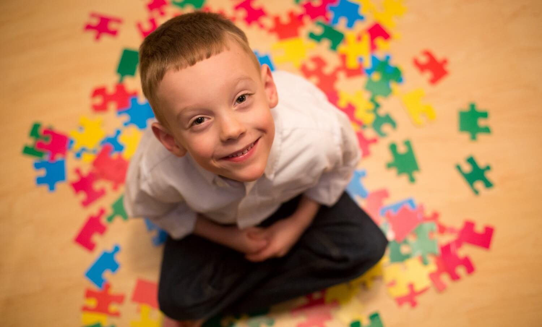 Niño con autismo sonriendo.