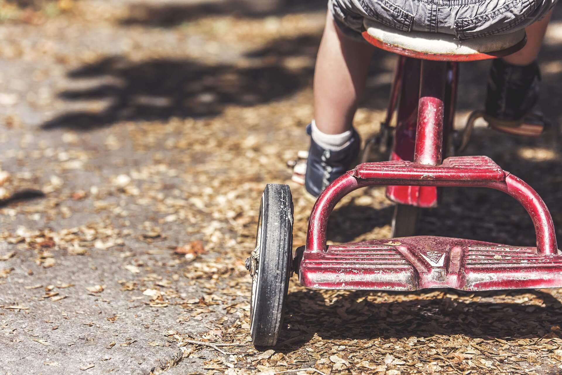 Les jambes d'un enfant sur un vélo.