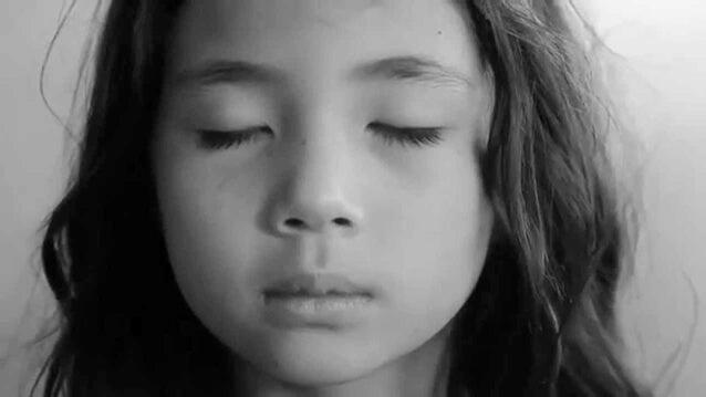 niña con los ojos cerrados aprendiendo a respirar profundo
