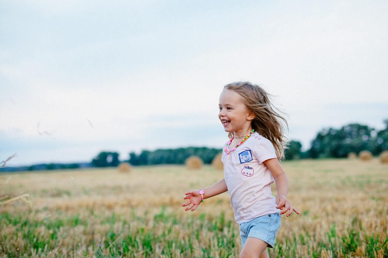 Nina corriendo por un prado feliz