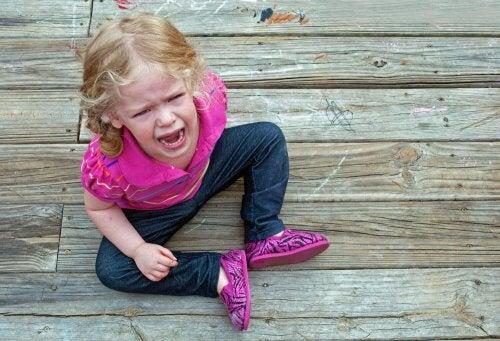 Niña de dos años sentada en el suelo llorando por una rabieta.