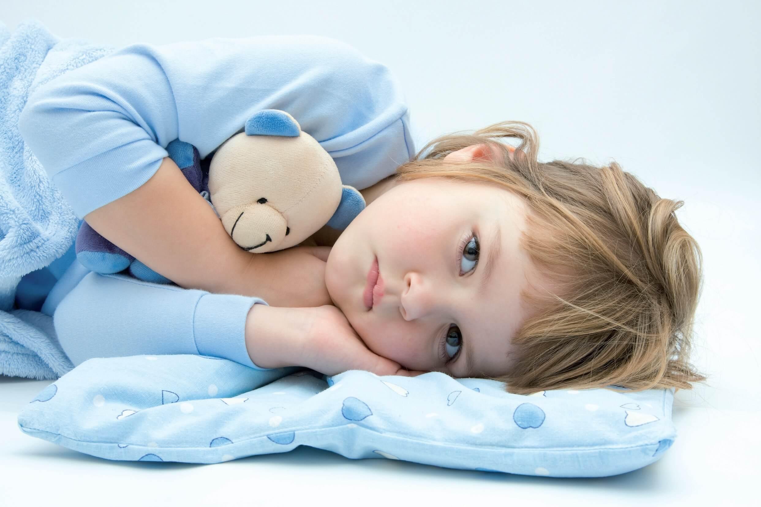 Nina despierta en la cama con pijama azul