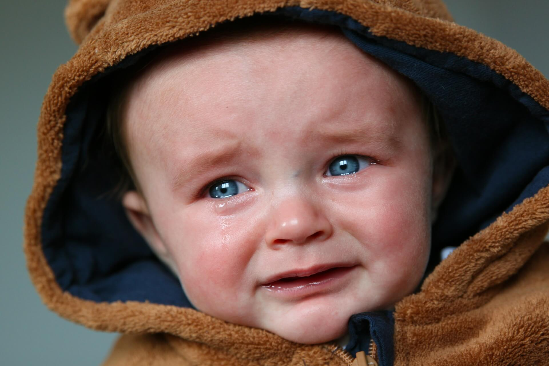Nino llorando con capucha marron