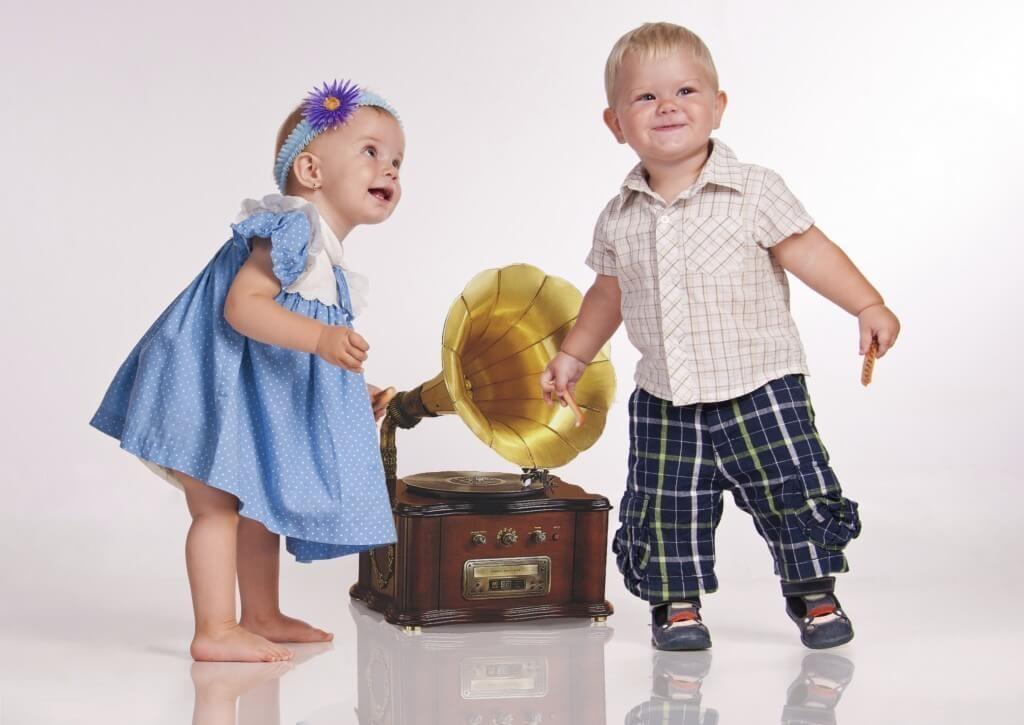 Un nino y una nina bailando con un gramofono