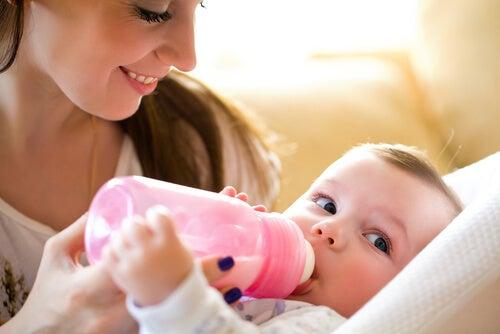 Madre dando el biberón esterilizado a su bebé