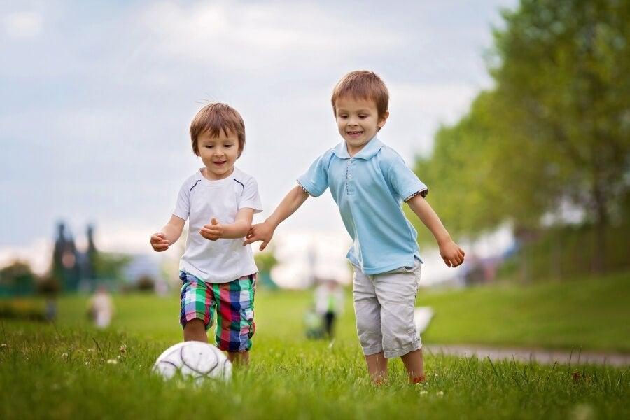 Ninos jugando al futbol en un parque