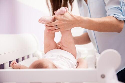 Madre cambiando el pañal a su bebé en un cambiador de ropa