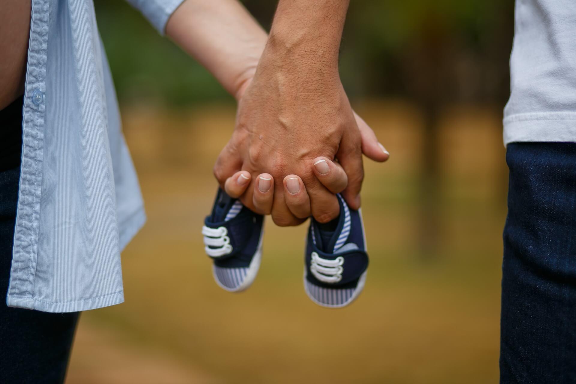 Padre y madre con las manos entrelazadas y unos zapatos de bebé