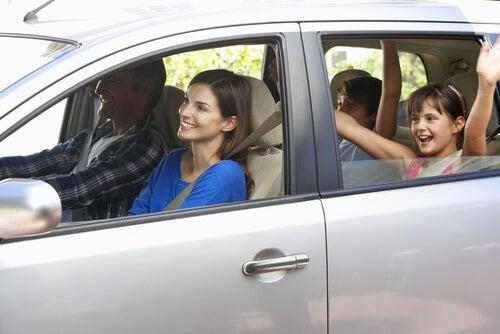 Familia feliz viajando cada uno en su asiento de coche