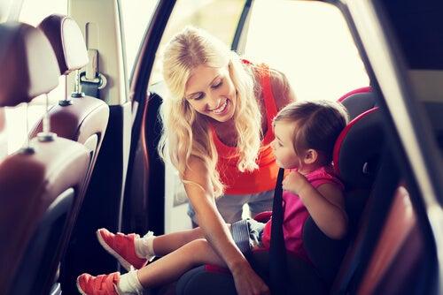 Madre atando el cinturón a su hijo en su sillita para el coche