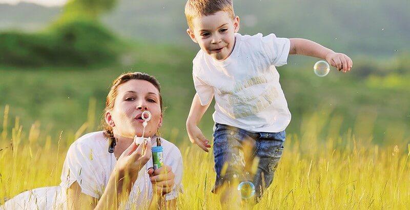 Madre e hijo en el campo haciendo pompas