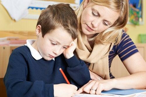 Profesora de apoyo en docencia compartida ayudando a un alumno en clase.