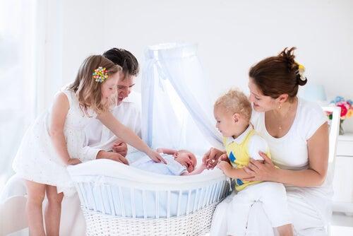 Familia alrededor de un bebé recién nacido que duerme en un moisés