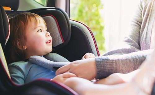 Padre atando a su hijo el cinturón de la silla del coche para poder viajar seguro