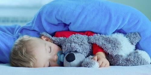 Bebé durmiendo con su peluche
