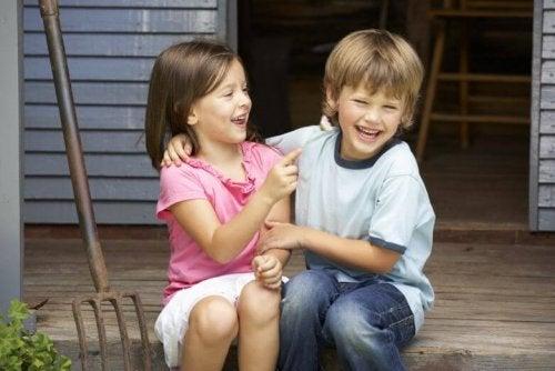 Dos hermanos sentados juntos y riendo