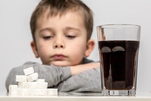 Niño mirando los terrones de azúcar que hay junto a su vaso de refresco con edulcorantes sintéticos.
