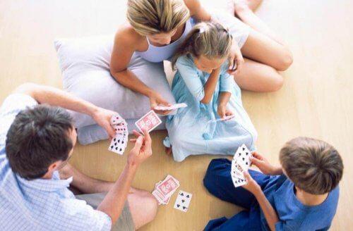 Familia jugando a las cartas con mucho amor.