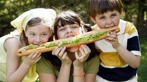 Tres hermanos compartiendo un bocadillo para evitar el síndrome del hermano mediano.