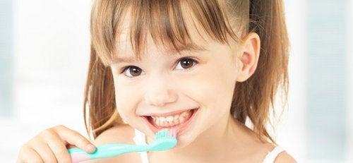 Niña lavándose los dientes mediante las técnicas de moldeamiento y encadenamiento.