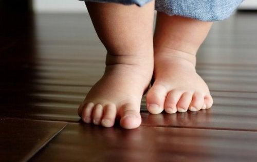 Bebé empezando a caminar con cuidado para no sufrir la fractura de los primeros pasos.
