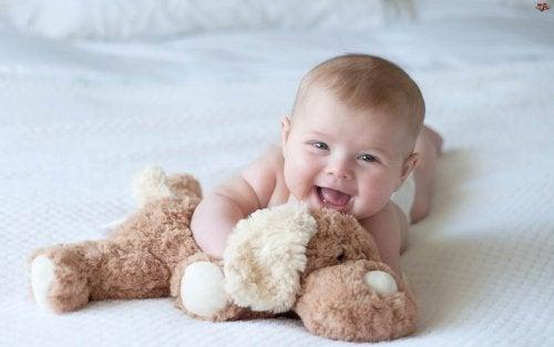 Un bebé apoyado sobre su abdomen con un peluche.