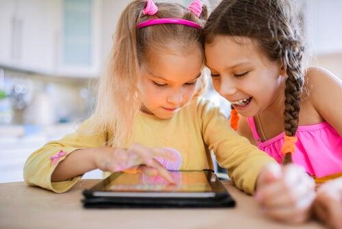Dos niñas jugando en línea con una tablet.