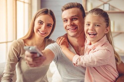 Una familia compartiendo frente a la TV con dibujos animados