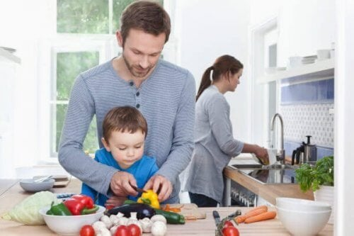 Niño en la cocina con sus padres, que hacen trabajo en equipo.