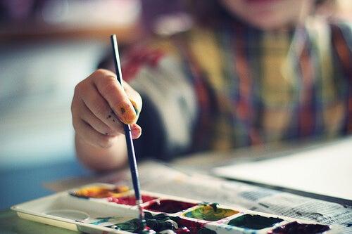 Niño pintando con acuarelas.