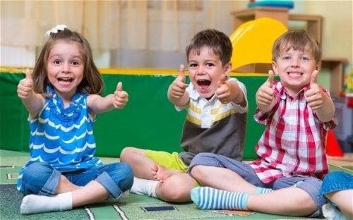 Niños con necesidad de aprobación levantando el pulgar.