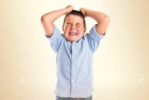 Niño llevándose las manos a la cabeza debido a la frustración infantil.