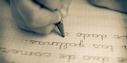 Niño escribiendo en su diario de gratitud como parte la escritura terapéutica para niños.