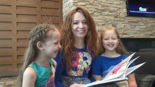 Madre e hijas leyendo un libro porque es muy importante la lectura durante la cuarentena.