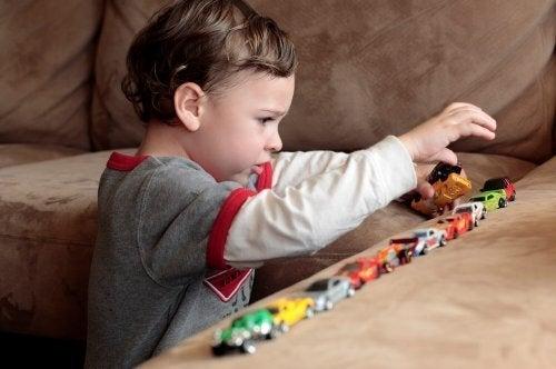 Niño con autismo jugando con unos coches de juguete.