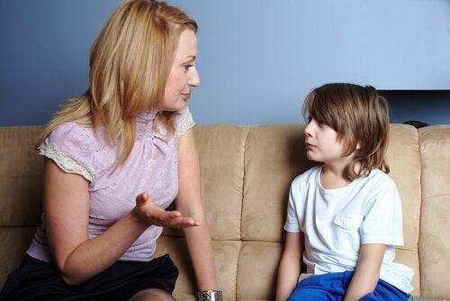 Niño hablando con su madre para evitar que interrumpa.