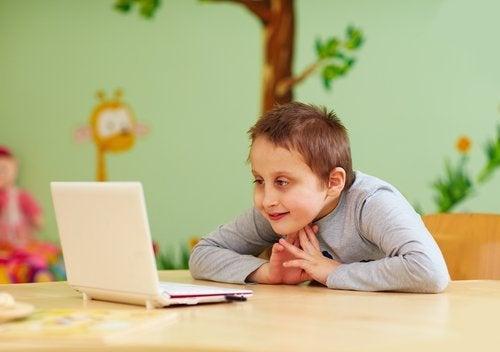 Niño con necesidad de cuidados especiales viendo algo en el ordenador.