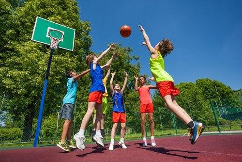 Niños jugando al baloncesto teniendo cuidado de no hacerse lesiones deportivas.
